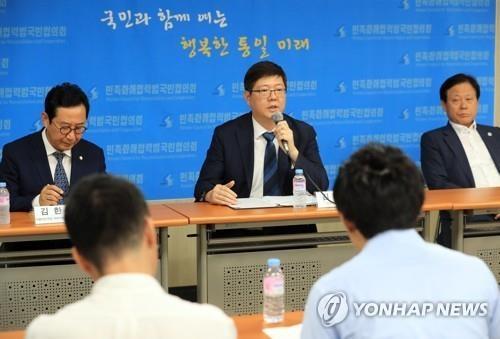 """7月22日,在韩国公民团体""""民族和解合作泛国民协议会""""办公室,民和协常任议长金弘杰(左二)向媒体记者介绍访朝结果。左一为共同民主党议员金汉正。(韩联社)"""
