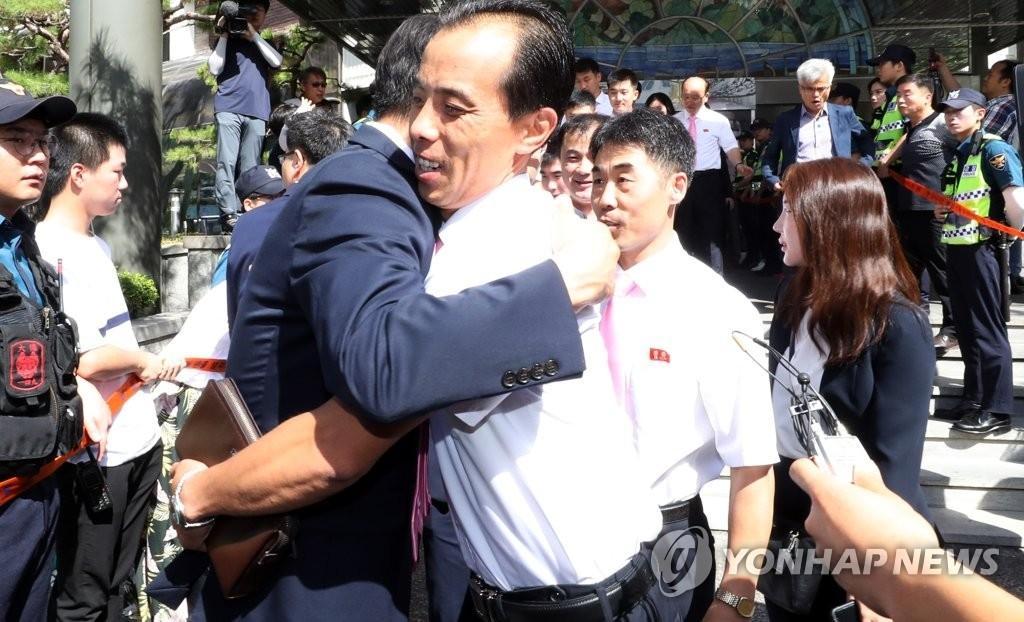 7月23日上午,在韩国大田,参加2018年国际乒联世界巡回赛韩国公开赛的朝鲜乒乓球代表团成员返朝前同韩方人员拥抱惜别。(韩联社)