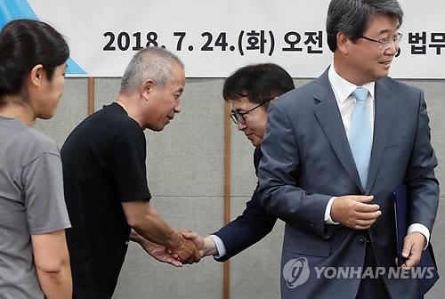 7月24日,半导体工人健康与人权守护组织代表(左二)和三星电子相关人士握手。(韩联社)