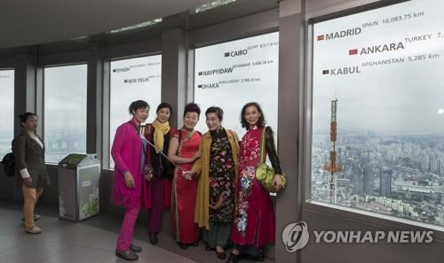 中国游客在塔上合影。(韩联社)