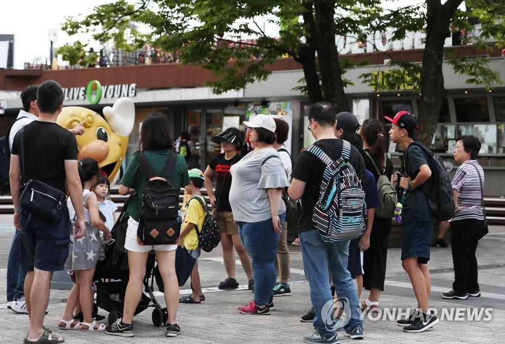 资料图片:7月30日,在N首尔塔前的广场,游客们正在听导游的介绍。(韩联社)