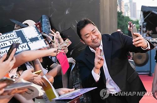 8月5日,在台湾举行的《与神同行2》红毯仪式上,演员马东锡与粉丝拍照。(韩联社/乐天娱乐提供)