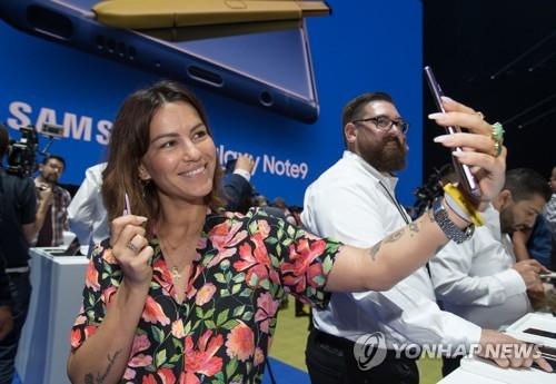 8月9日,在纽约举行的Galalxy Note9发布会上,一名女性全验Galaxy Note9。(韩联社)