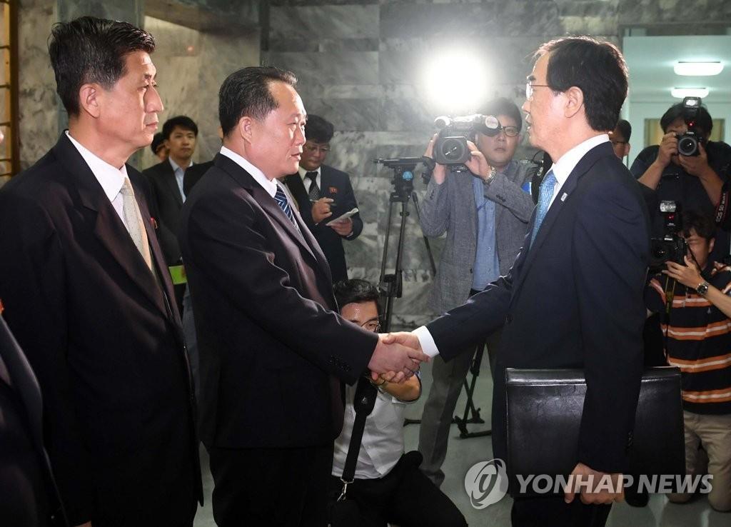 赵明均(右)和李善权在会谈前握手。(韩联社)
