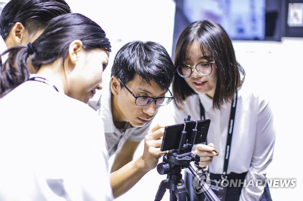 8月15日,在上海举行的Note9发布会上,当地用户正在体验手机功能。(韩联社)