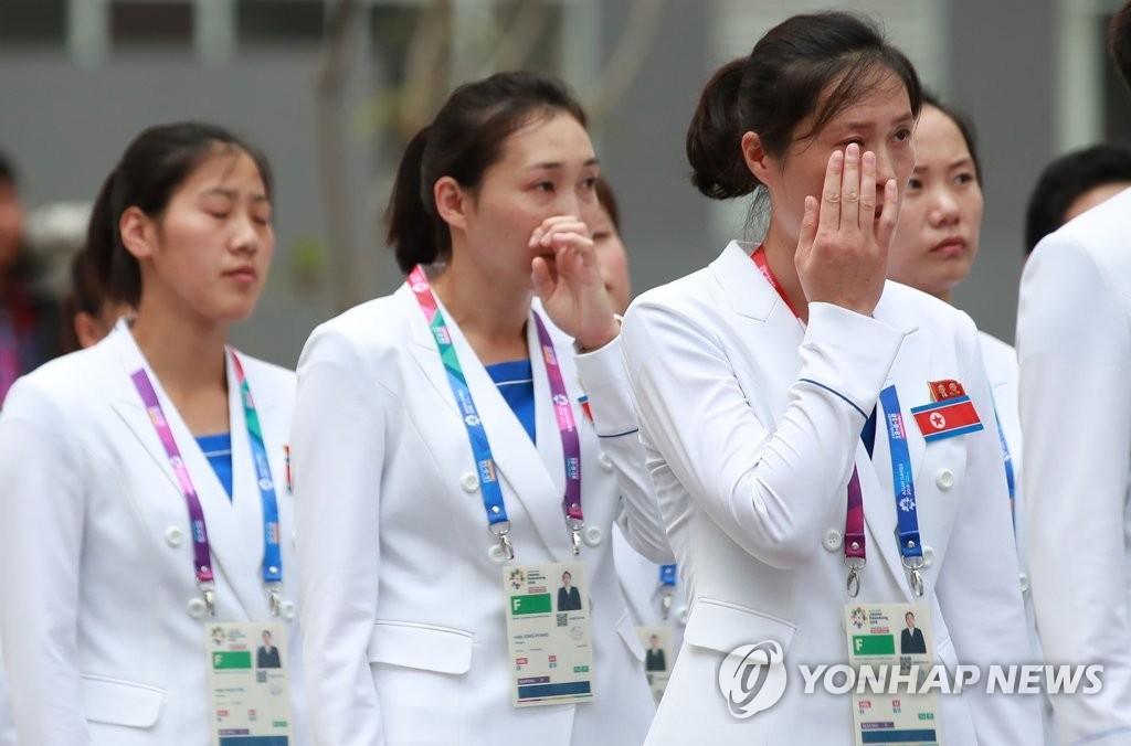 8月16日,朝鲜亚运代表团入村仪式在印尼雅加达举行,朝鲜女子手球运动员在升国歌、奏国歌时激动落泪。(韩联社)