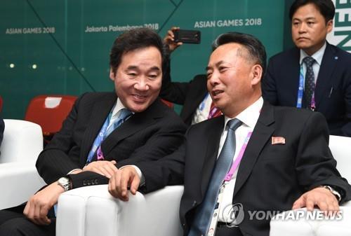 当地时间8月18日下午,2018雅加达亚运会开幕式在印尼雅加达朋加诺体育场举行,韩国国务总理李洛渊(左)与朝鲜内阁副总理李龙男在开幕式上亲密交谈。(韩联社)