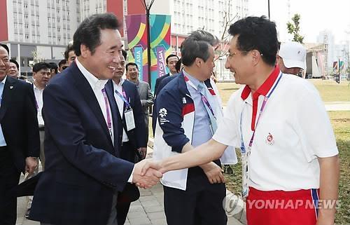 8月19日,在雅加达,李洛渊(左)同元吉友握手致意。(韩联社)