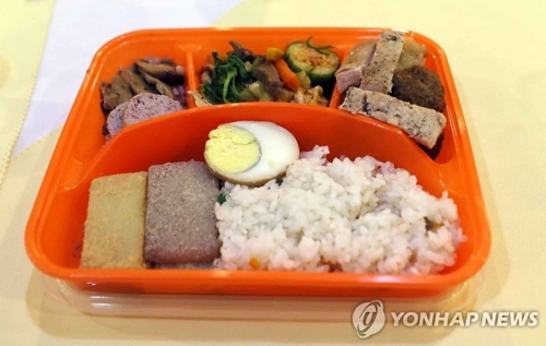 8月21日,在朝鲜外金刚山酒店,朝方酒店服务员向参加韩朝离散家属团聚单独会面的各韩方亲属客房分发盒饭。(韩联社)