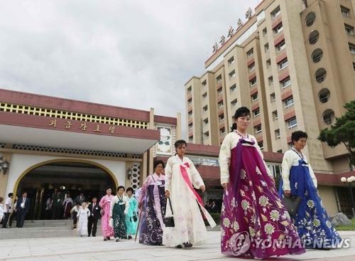 8月21日,在朝鲜外金刚山酒店,朝方亲属在参加韩朝离散家属团聚单独会面活动后准备乘巴士返回。(韩联社)