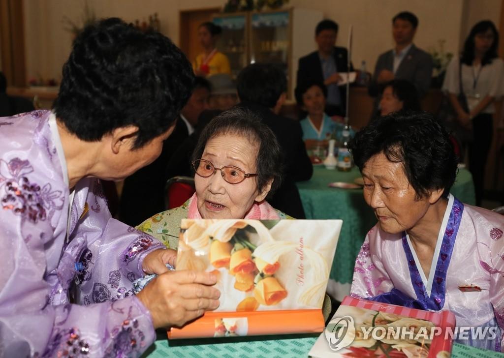 8月21日,第21次韩朝离散家属团聚活动在朝鲜金刚山举行。图为韩方99岁高龄的韩信子与两个在朝女儿翻看相册。(韩联社)