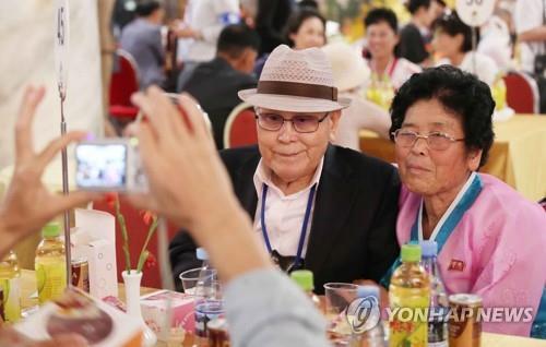 资料图片:8月21日,第一轮韩朝离散家属团聚活动在朝鲜金刚山酒店举行,图为韩方父亲(89岁,左)在晚宴上同朝方女儿(67岁)合影。(韩联社)