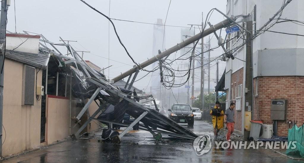 """8月23日,第19号台风""""苏力""""登陆韩国济州,济州市区一处道路上的电线杆被狂风吹倒,造成周边建筑物部分损毁和停电。(韩联社)"""