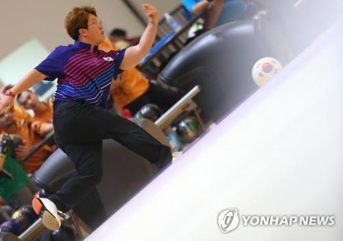 8月25日,在保龄球男子六人队际赛中,韩国队选手崔福音(音)打球。(韩联社)