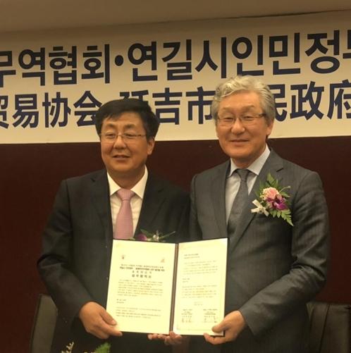 延吉市长蔡奎龙(左)和世界韩人贸易协会会长朴己出在签约仪式后合影留念。(韩联社)