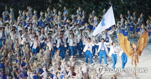 资料图片:8月18日,在2018雅加达亚运会开幕式上,韩朝代表团举韩半岛旗共同入场。(韩联社)