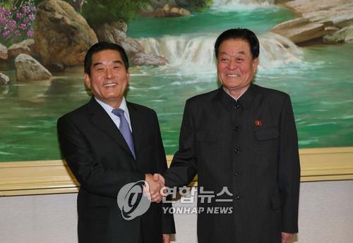 资料图片:2007年10月12日下午,在平壤市人民文化宫殿,时任韩联社社长金基瑞(左)同朝中社社长金基龙见面握手。这是韩朝新闻通讯社社长第一次会面。(韩联社)