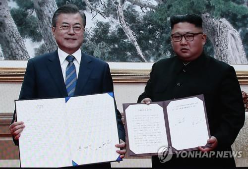 9月19日上午,在平壤百花园国宾馆,韩国总统文在寅(左)和朝鲜国务委员会委员长金正恩签署《平壤共同宣言》。图为韩朝首脑会谈主新闻中心报道画面截图。(韩联社)