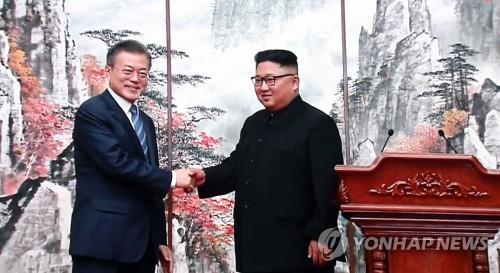 9月19日,在平壤百花园国宾馆,韩国总统文在寅(左)和朝鲜国务委员会委员长金正恩握手。图为首尔韩朝首脑会谈新闻中心播出的视频截图。(韩联社)