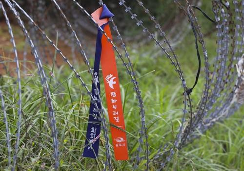 """海峡铁丝网防线上绑着写有""""和平世界路""""字样的布条。(韩联社记者成演在摄)"""