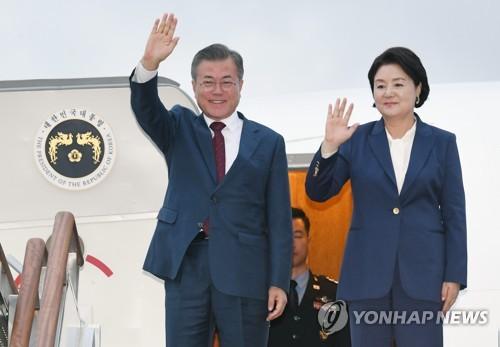 9月20日,在位于京畿道城南市的首尔机场,韩国总统文在寅(左)和夫人金正淑在舷梯口向迎接人群挥手致意。文在寅当天结束为期三天的访朝行程回国。(韩联社)