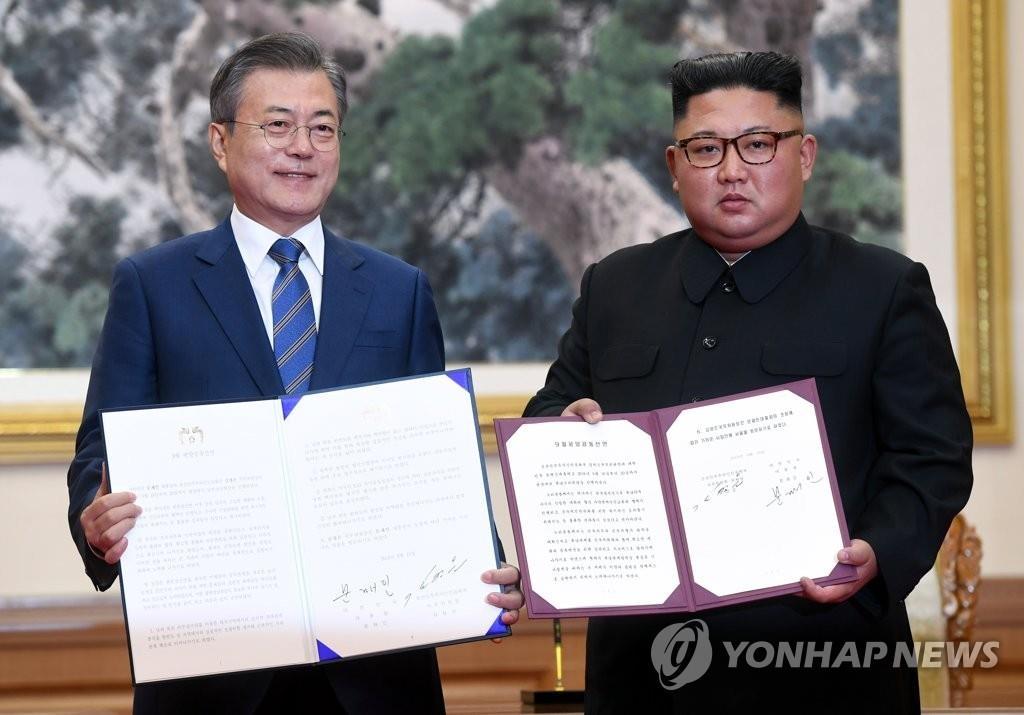 资料图片:9月19日上午,在平壤百花园国宾馆,韩国总统文在寅(左)和朝鲜国务委员会委员长金正恩签署《平壤共同宣言》。(韩联社)