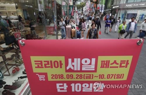 资料图片:9月28日,首尔明洞街头挂出韩国购物旅游体验节宣传广告。(韩联社)