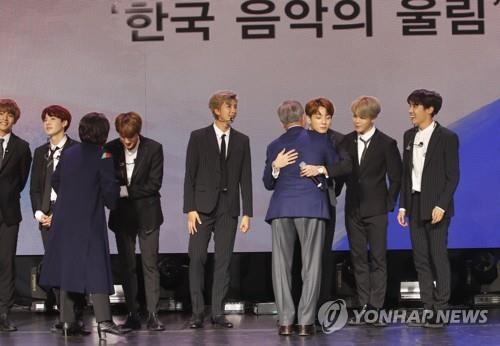 """当地时间10月14日下午,在法国巴黎,韩国总统文在寅在""""韩法友谊演唱会""""结束后登台与防弹少年团成员拥抱。(韩联社)"""