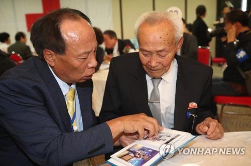 资料图片:8月24日下午,在朝鲜金刚山,在朝父亲赵德容(右)与在韩儿子赵政基(左)父子一同翻看相册。(韩联社)