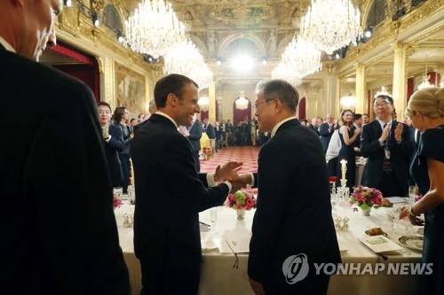 当地时间10月15日,在法国总统府爱丽舍宫,韩国总统文在寅(右)在法方举办的国宴上与法国总统马克龙握手。(韩联社)