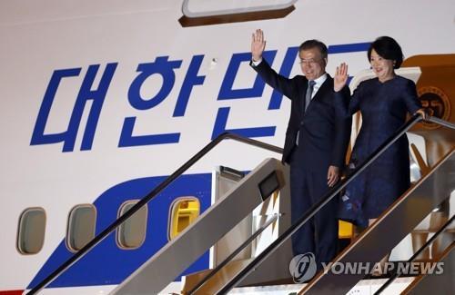 当地时间10月16日下午,韩国总统文在寅(左)和夫人金正淑女士抵达罗马菲乌米奇诺机场后向前来迎接的人群挥手致意。(韩联社)