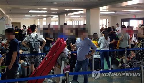 10月28日,在塞班国际机场韩亚航空值机柜台,等待办理登机手续的乘客排起长龙。(韩联社/读者供图)