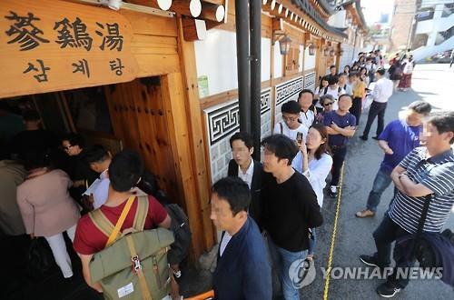 资料图片:一家参鸡汤店前食客排长龙。(韩联社)