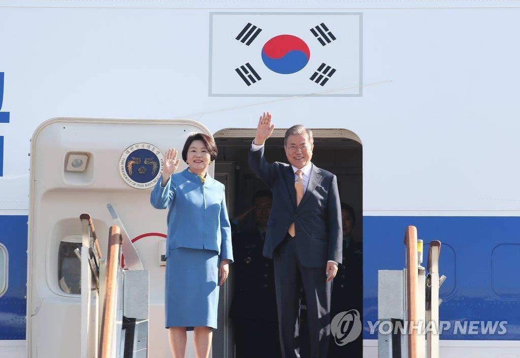 资料图片:11月13日,在京畿道城南首尔机场,韩国总统文在寅(右)携夫人金正淑启程前往新加坡。图为文在寅夫妇向前来送行的人群挥手致意。(韩联社)