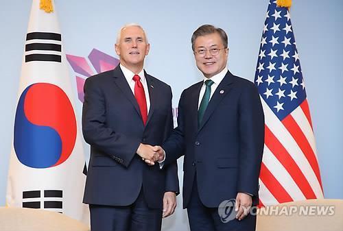 当地时间11月15日上午,在新加坡新达城国际会议展览中心,为出席东盟系列峰会而正在新加坡访问的韩国总统文在寅(右)与美国副总统彭斯在会晤前握手合影。(韩联社)