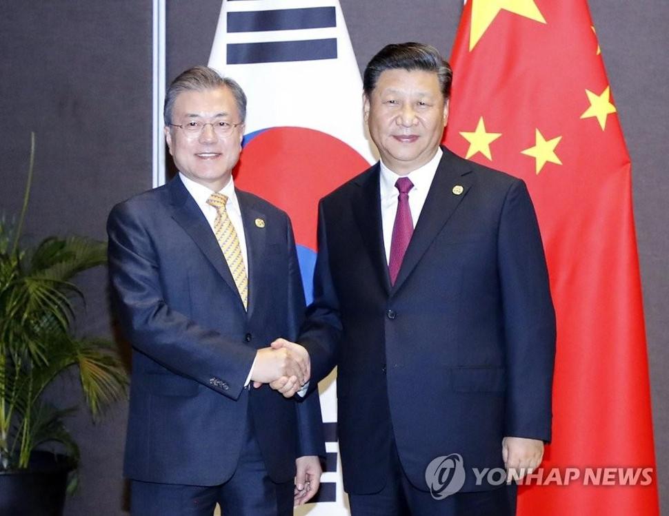资料图片:11月17日,在巴布亚新几内亚莫尔兹比港,韩国总统文在寅(左)与中国国家主席习近平在举行会晤前握手合影。(韩联社)