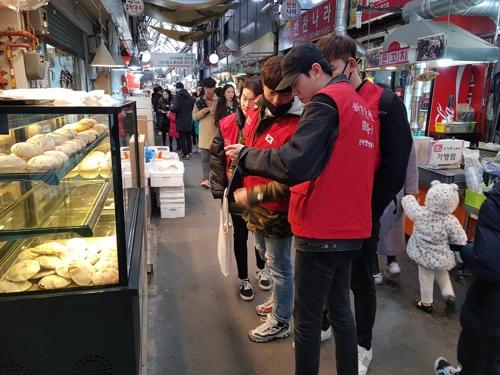 资料图片:新罗免税店中国留学生志愿服务团成员们在首尔通仁市场开展志愿活动。(韩联社/新罗免税店供图)