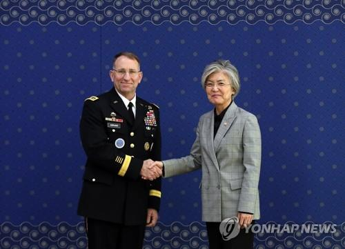 11月20日下午,在韩国外交部,康京和与艾伯拉姆斯握手。(韩联社)