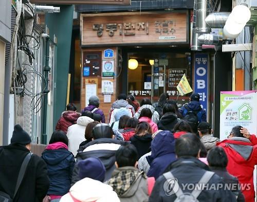 资料图片:中国游客在春川明洞烤鸡排胡同前排起长龙。(韩联社)