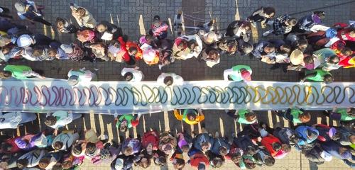10月20日下午,在利川大米文化节上,众人齐拉600米长的飘香米糕条。(韩联社记者成演在摄)