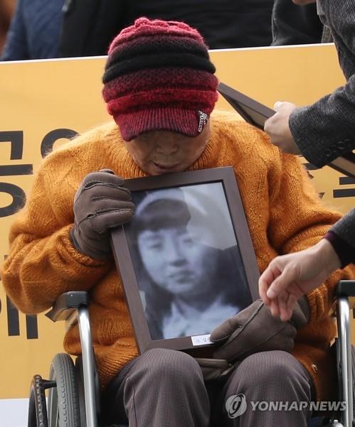 """11月29日上午,在首尔瑞草区大法院前,二战期间被强征到日本的""""朝鲜女子勤劳挺身队""""受害者金圣株(音)手捧已去世的另一名受害者遗像等待宣判结果。(韩联社)"""