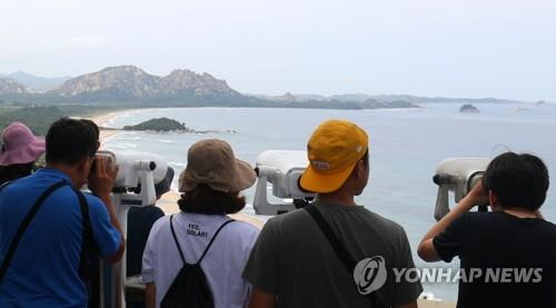 资料图片:8月19日,在江原道高城郡统一瞭望台,韩国游客眺望金刚山。(韩联社)