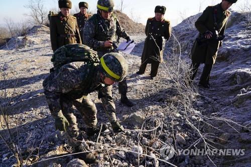 资料图片:12月12日,在军事分界线附近,韩国检查组检查朝方哨所拆除情况。(韩联社/国防部供图)