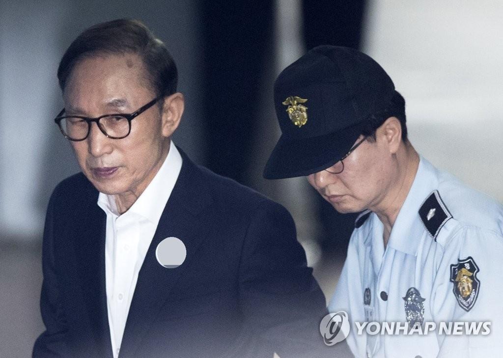 前总统李明博(左)走向法庭。(韩联社)