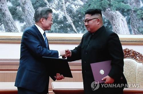 资料图片:9月19日,在韩朝首脑会谈上,韩国总统文在寅(左)和朝鲜国务委员会委员长金正恩握手致意。(韩联社)