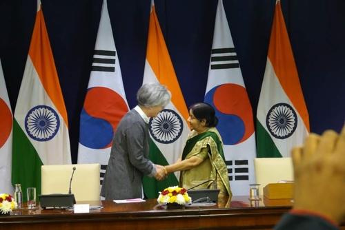 12月19日,在印度新德里,韩国外交部长官康京(左)同印度外交部长苏什玛·斯瓦拉杰握手致意。(韩联社)