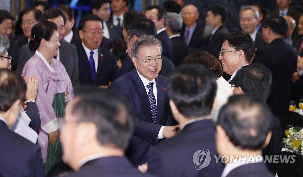 1月2日,在首尔中小企业中央会大楼,韩国总统文在寅出席迎新会与与会人士握手致意。(韩联社)