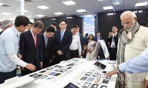 资料图片:2018年7月9日,韩国总统文在寅(前排左二)和印度总理莫迪(右一)在三星电子副会长李在镕(前排左四)陪同下出席三星在印度诺伊达新建工厂的落成仪式。(韩联社)