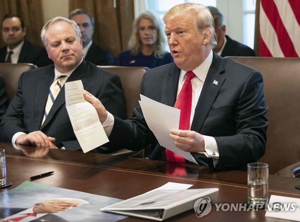 当地时间1月2日,美国总统特朗普(右)在白宫主持召开内阁会议时手持金正恩亲笔信。(韩联社/法新社)