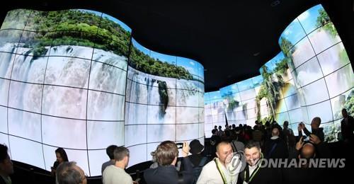 资料图片:当地时间2018年1月9日,在拉斯维加斯,LG电子在CES上打造的展馆挤满了访客。(韩联社)